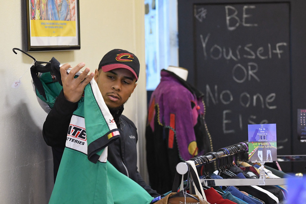 . Eric Bonzar�The Morning Journal<br> A customer checks out a vintage Interstate Batteries NASCAR shirt from the collection of Twenty-year-old Reinaldo Contreras III, of Lorain, during Contreras\' RICHES 2 RELICS pop up shop to Jevon Terance Boutique, 615 Broadway Ave., Feb. 16, 2017. Contreras will also be on hand to fill all your vintage ware needs, from 10 a.m. to 6 p.m., Feb. 17.