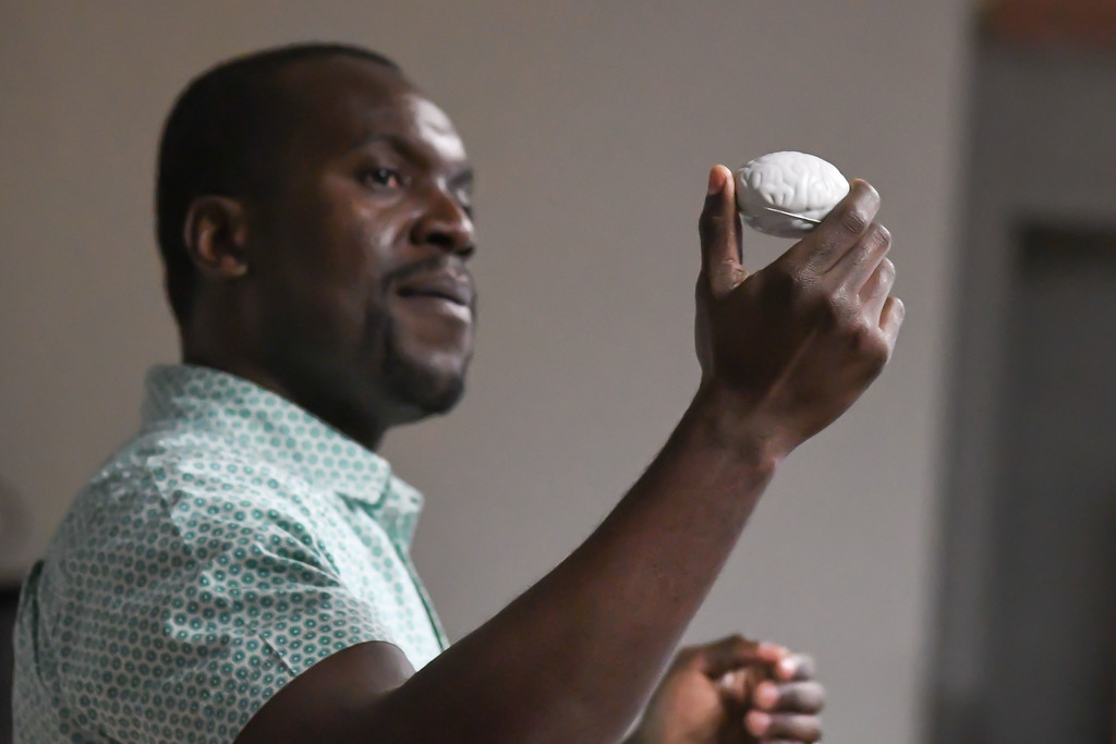 . Eric Bonzar�The Morning Journal<br> Oberlin College assistant professor Gunnar Kwakye uses a squishy stress ball, shaped like a brain, to explain its sections and their purpose to children during Get with the Program\'s Brain Games event, Feb. 19, 2018.