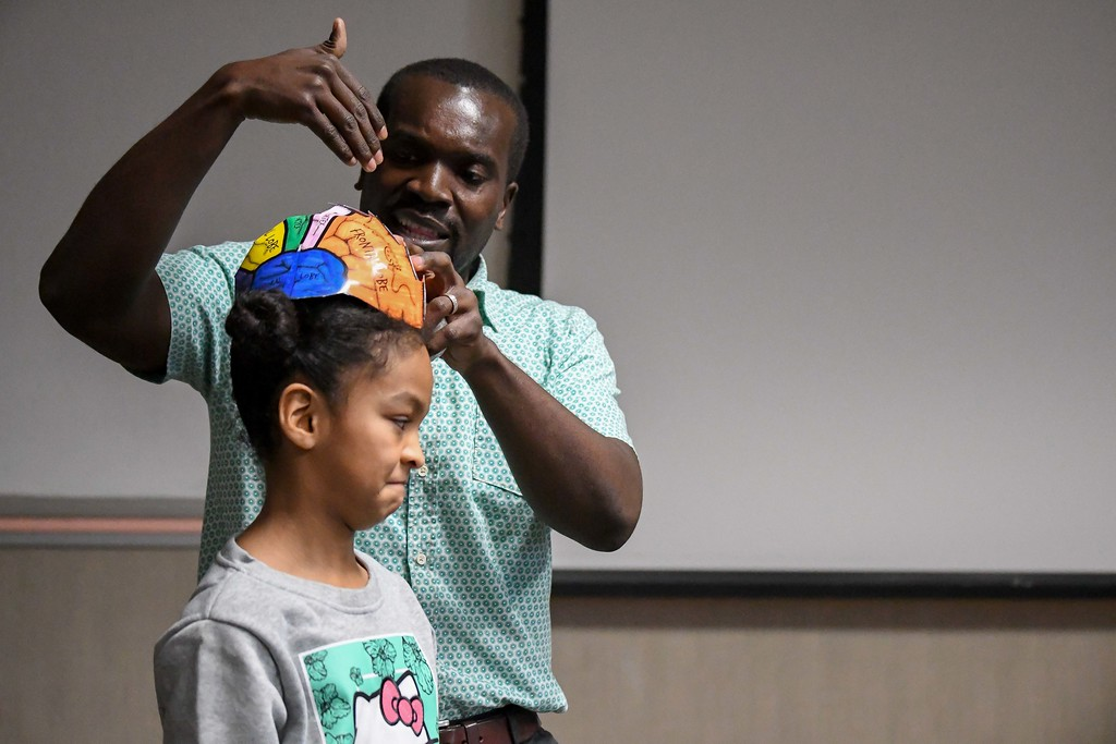 """. Eric Bonzar�The Morning Journal<br> Ten-year-old Jaylynn Williams, of Oberlin, wears a brain hat as Oberlin College assistant professor Gunnar Kwakye \""""dissects\"""" the sections and explains their purpose to children during Get with the Program\'s Brain Games event, Feb. 19, 2018."""