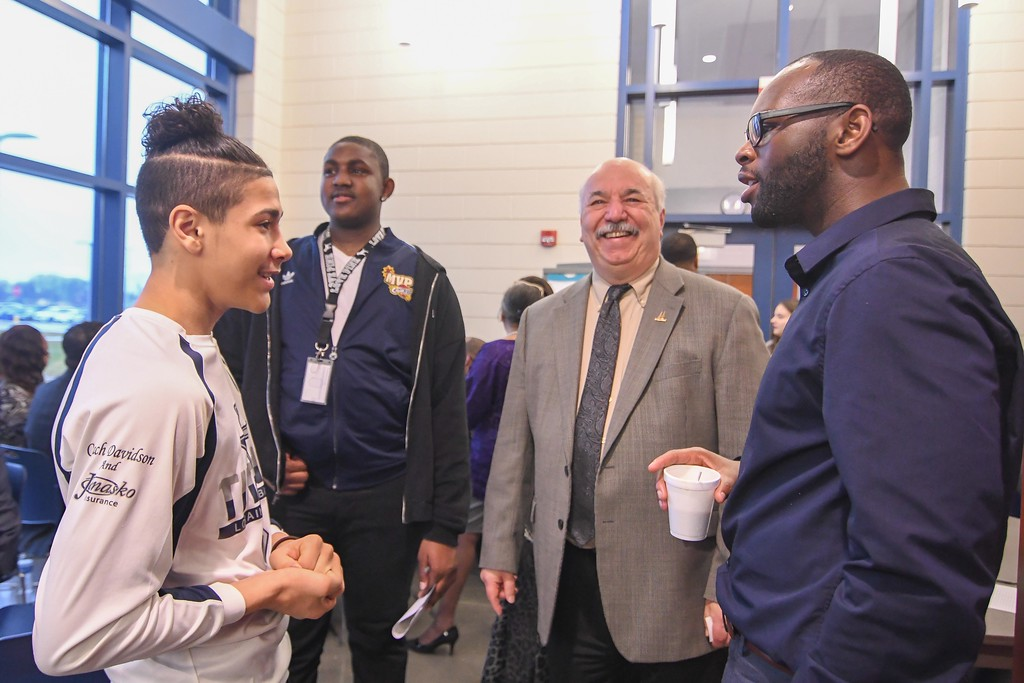 . Eric Bonzar�The Morning Journal<br> Lorain High School scholars Jesse Robles, 15, left, and Jerrod Jackson, 15, chat with Elyria Ward 5 Councilman Marcus Madison, right, and Lorain Police Chief Cel Rivera during Lorain City Schools\' Community Business Schools partnership meeting, Feb. 21, 2018.