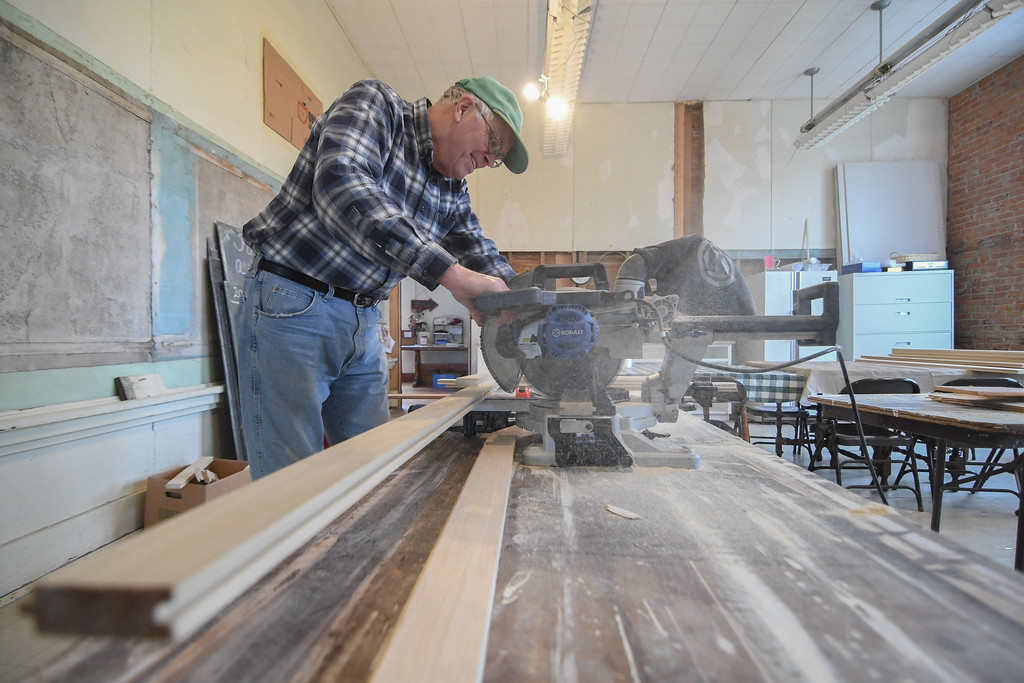 . Eric Bonzar�The Morning Journal Bob Leimbach, vice president of the Brownhelm Historical Association and a former student of Brownhelm School, cuts wainscoting to length, Feb. 27, 2017. Leimbach, members of the historical association, and residents of the small community have come together to restore the school, which closed its doors in 1988.