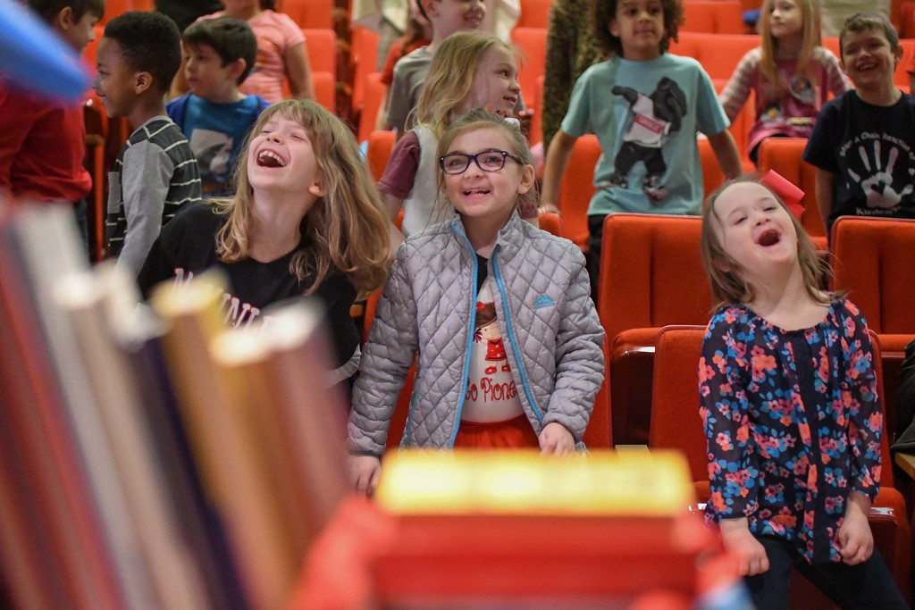 . Eric Bonzar�The Morning Journal<br> From left: Seven-year-old McKinley Elementary School first-graders Lilah Foucher and Claire Leitner, and 8-year-old second-grader Cameryn Culvier dance along during the unveiling of the Little Free Library at UH Elyria Medical Center, April 10, 2018.