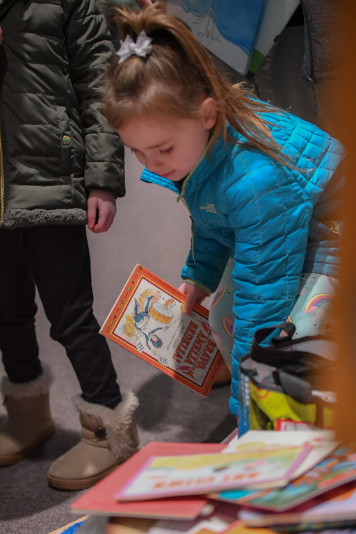 . Eric Bonzar�The Morning Journal<br> A McKinley Elementary School student sets down her contribution during the unveiling of the Little Free Library at UH Elyria Medical Center, April 10, 2018.