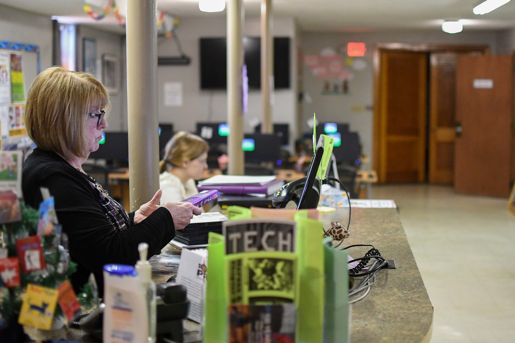 . Eric Bonzar�The Morning Journal<br> Library Technician Denise Deery checks items back into the system, April 16, 2018. Elyria Public Library System\'s South Branch currently operates out of the basement of the Asbury United Methodist Church, 1611 Middle Ave. after its previous home shared with Lorain County Community Action Agency Head Start, located at 1215 Middle Ave., was demolished.