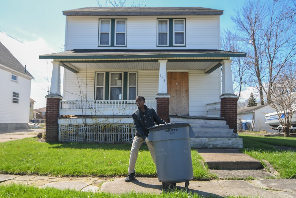 """. Eric Bonzar�The Morning Journal<br> Twelve-year-old Dwele Thompson uses brute force to lug a trash can past a vacated residence on West 31st Street, April 26, 2018. Thompson and his fellow fifth grade classmates picked up trash around their school and neighborhood as part of Pay it Forward Day, and in honor of Lorain native and Garfield Elementary School alumna Theresa \""""Tippie\"""" Moon and the To the Moon & Back Foundation."""