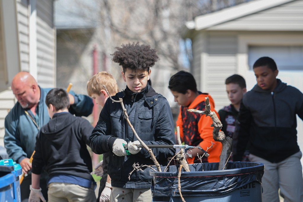 """. Eric Bonzar�The Morning Journal<br> Twelve-year-old Antonio Lahens and his fellow classmates clean up debris around residents\' homes near Garfield Elementary School, April 26, 2018. The fifth graders picked up trash around their school and neighborhood as part of Pay it Forward Day, and in honor of Lorain native and Garfield Elementary School alumna Theresa \""""Tippie\"""" Moon and the To the Moon & Back Foundation."""
