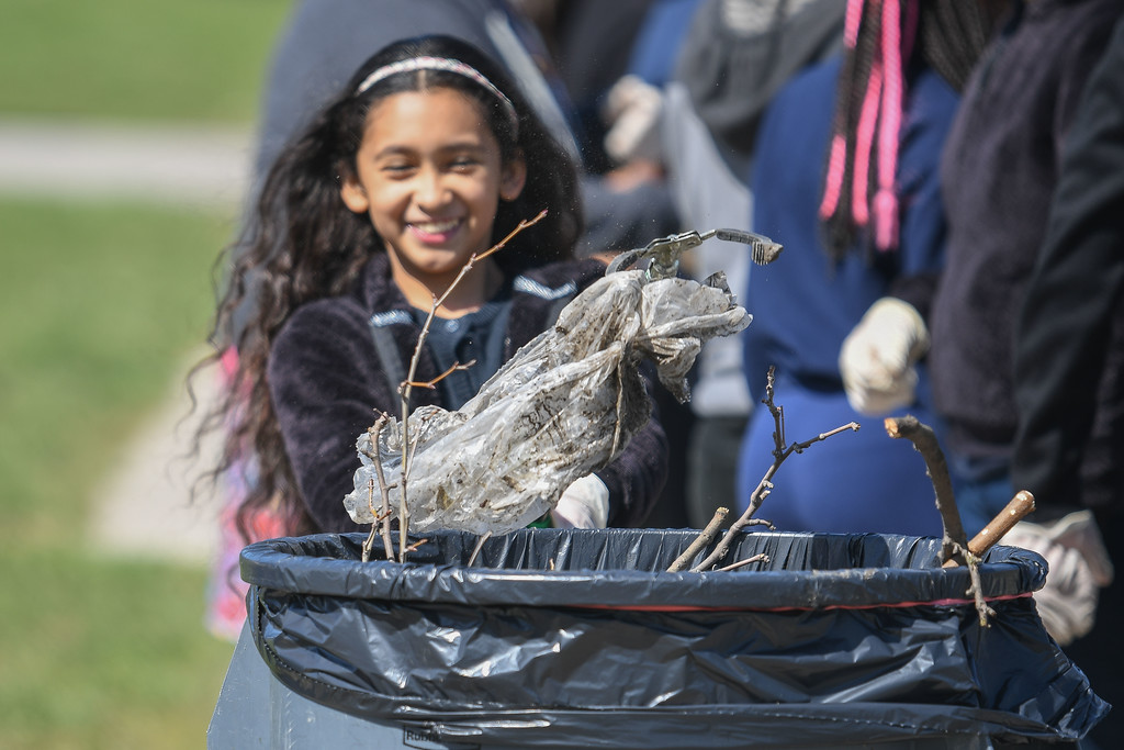 """. Eric Bonzar�The Morning Journal<br> Ten-year-old Stephanie Vargas is all smiles as she and her fellow classmates clean up debris around Garfield Elementary School, April 26, 2018. The fifth graders picked up trash around their school and neighborhood as part of Pay it Forward Day, and in honor of Lorain native and Garfield Elementary School alumna Theresa \""""Tippie\"""" Moon and the To the Moon & Back Foundation."""