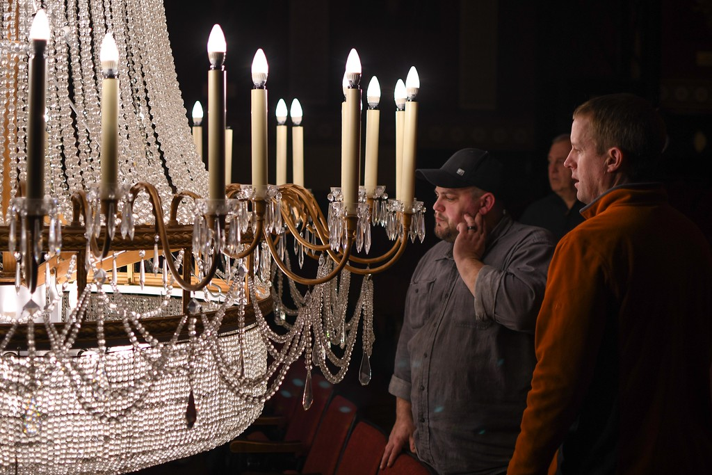 . Eric Bonzar�The Morning Journal<br> Theater Technician Andy Hartman, right, and Technical Director Isaac Thompson check out the condition of the Lorain Palace Theater chandelier, March 7, 2018. Staff lowered the 3/4 ton, 87 bulb, Yugoslavian cut crystal chandelier for maintenance, Wednesday morning. The theater plans to leave the chandelier down until about March 22, and encourage fans to stop by from 9 a.m. to 3 p.m., Tues. through Friday to see it up close and personal.