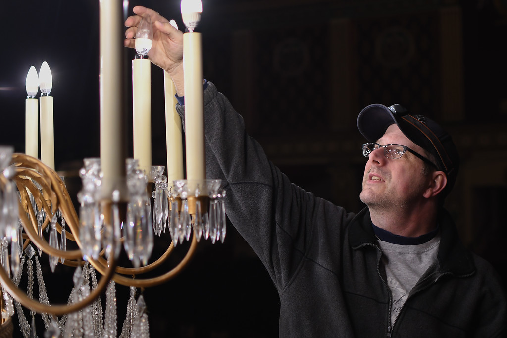 ". Eric Bonzar�The Morning Journal<br> Maintenance worker Ed Urban checks the ""cattywampus\""-ness of a light bulb while inspecting the Lorain Palace Theater\'s chandelier, March 7, 2018."