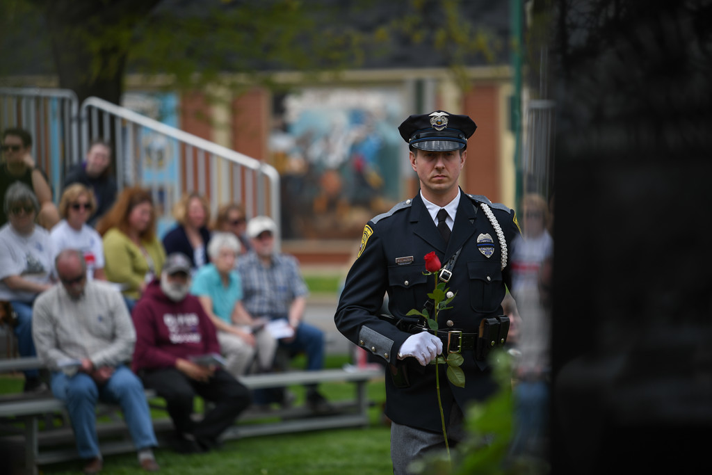 . Eric Bonzar�The Morning Journal<br> Lorain police Officer Eric Alten places a red rose at the base of the Wellington Safety Forces Memorial, in honor of a fallen officer, during the Lorain County Police Memorial, held at Howk Memorial Park, in Wellington, May 10, 2018.