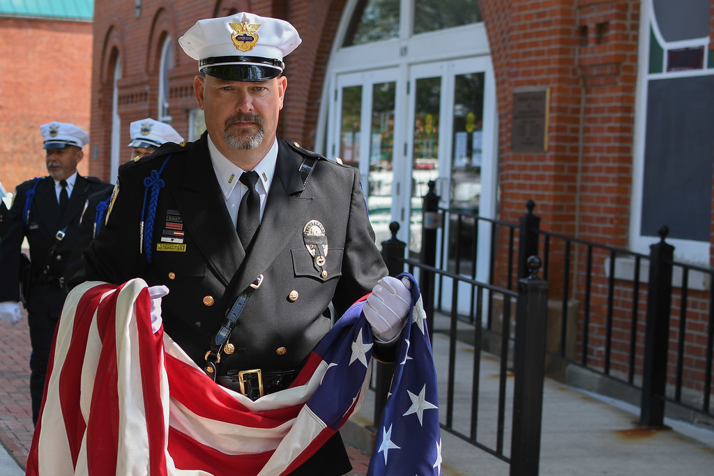 . Eric Bonzar�The Morning Journal<br> Wellington police Lt. Jeff Shelton carries the American flag before it is raised to half-staff during the Lorain County Police Memorial, held at Howk Memorial Park, in Wellington, May 10, 2018.