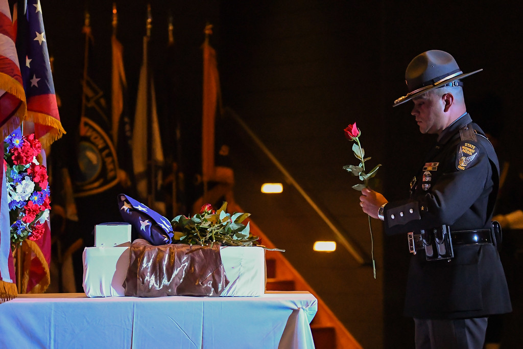 . Eric Bonzar�The Morning Journal An Ohio State Highway Patrol Trooper lays a red rose in remembrance of fallen Trooper Kenneth Velez, who was killed in the line of duty on Sept. 15, 2016.
