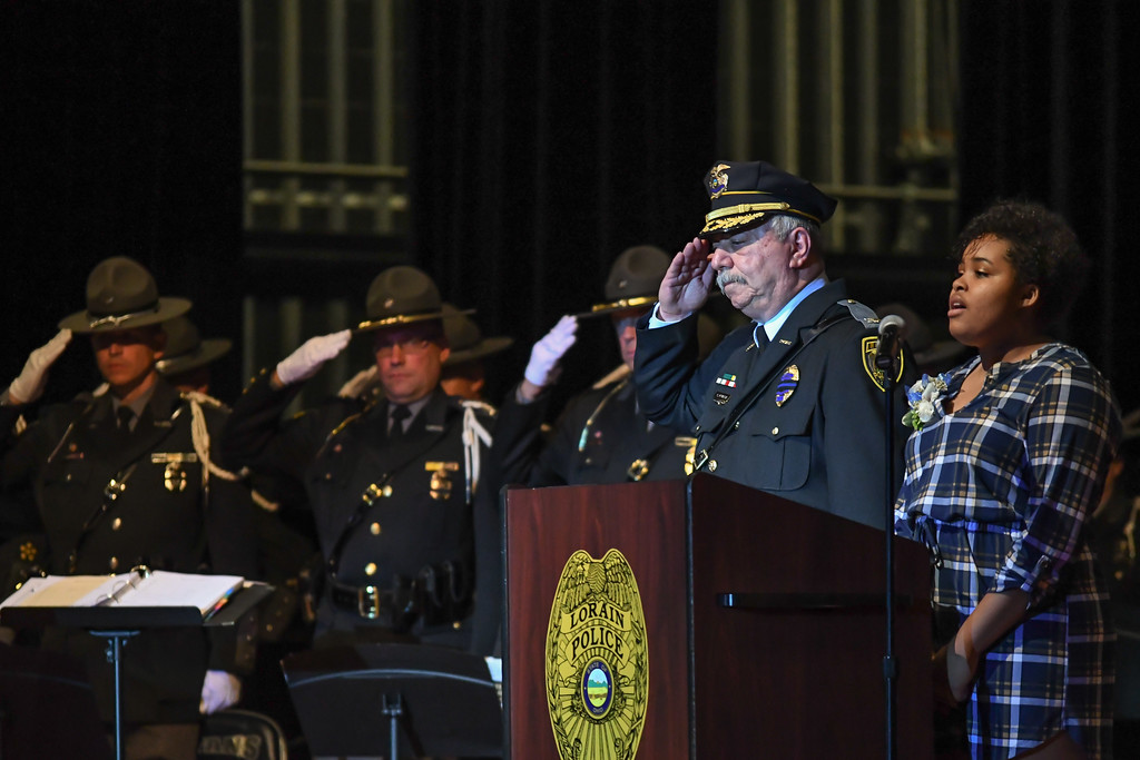 . Eric Bonzar�The Morning Journal Lorain High School student Anastasia Williams sings the National Anthem, alongside Lorain Police Chief Cel Rivera, during the Lorain County Police Memorial Service, May 11, 2017.