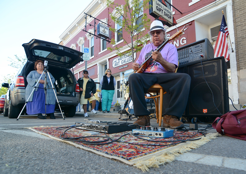 "Eric Bonzar—The Morning Journal<br /> Pedro ""Guitarman"" Diaz busks out front of Lee's Landing Gift Shop, during Vermilion's 11th annual 3rd Thursday: Music Flowers and a Sunset event, May 19, 2016."