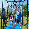 """Eric Bonzar—The Morning Journal<br /> Fourth-grader Sarah Karabatsos, 10,  swings on the gymnastic rings while completing the fourth annual """"Rock the Challenge"""" obstacle course at Holy Trinity School, 2610 Nagel Road, Avon, May 23, 2016."""