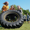 """Eric Bonzar—The Morning Journal<br /> From left to right: 11-year-olds Madison Kruz, Anna Powers and Charlie Campbell use teamwork to flip an industrial tire while completing the fourth annual """"Rock the Challenge"""" obstacle course at Holy Trinity School, 2610 Nagel Road, Avon, May 23, 2016."""