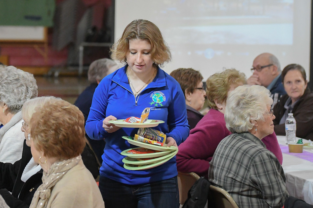 """. Eric Bonzar�The Morning Journal Firelands High School senior Gianna Suglia, 18, clears tables as guests mingle during the \""""Lunch and a Show\"""" event held at South Amherst Middle School, March 28, 2017. The afternoon event provided an opportunity for students to interact with seniors within the community, by offering a luncheon and a performance of \""""Princess Whatsername\"""" by the seventh and eighth grade choirs."""