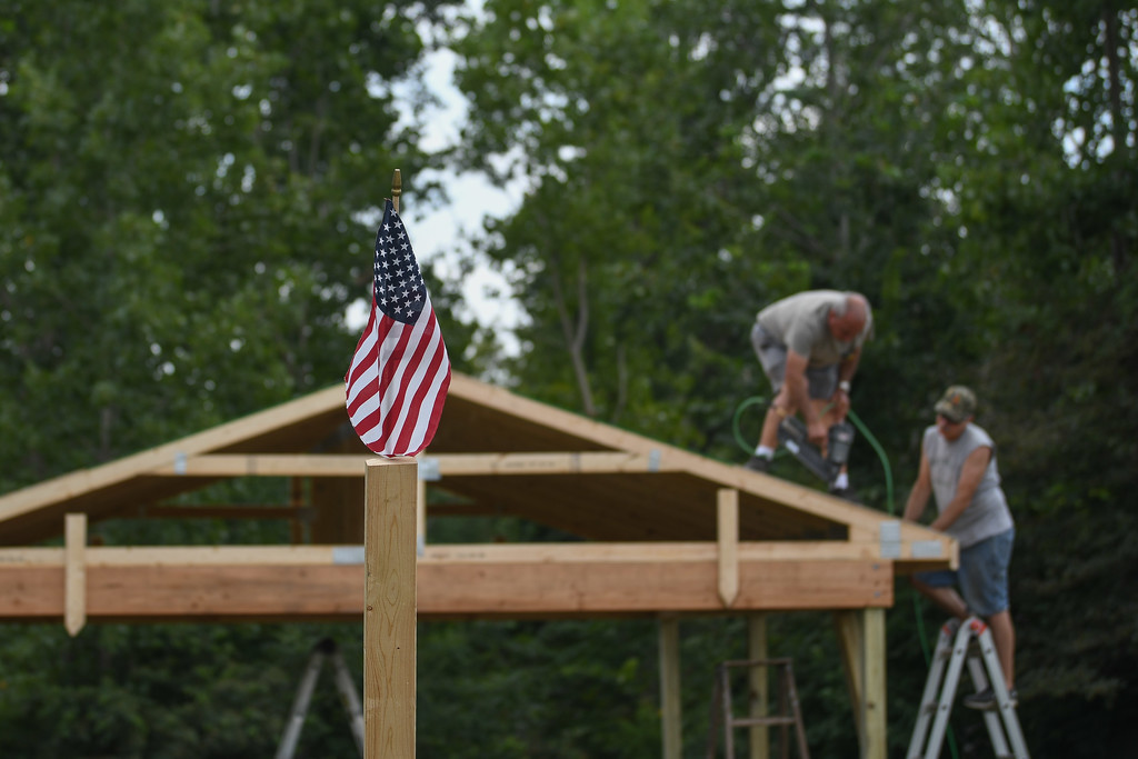 . Eric Bonzar�The Morning Journal Volunteer John McKiel, left, and  Vietnam veteran John Sekletar, right, work with to cover the roof of the Vietnam Veterans Memorial of Lorain County pavilion, 625 N. Lake St., Amherst, July 26, 2017. Through the fundraising efforts of the American Slovak Club, in Lorain, and the countless volunteers and military veterans who have dedicated their time and talents, visitors of the memorial will now have a place to relax and reflect as they pay their respects to the 98 servicemen who lost their lives during the war.