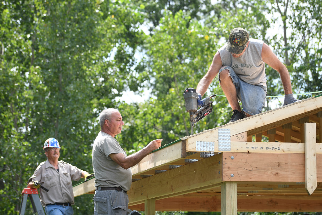 . Eric Bonzar�The Morning Journal Vietnam veterans Joe Horvath, left, and John Sekletar, right, work with volunteer John McKiel to cover the roof of the Vietnam Veterans Memorial of Lorain County pavilion, 625 N. Lake St., Amherst, July 26, 2017. Through the fundraising efforts of the American Slovak Club, in Lorain, and the countless volunteers and military veterans who have dedicated their time and talents, visitors of the memorial will now have a place to relax and reflect as they pay their respects to the 98 servicemen who lost their lives during the war.