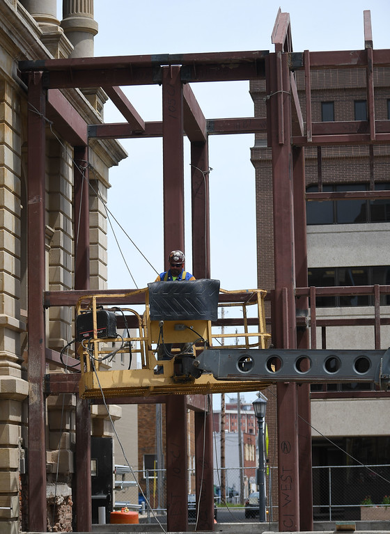 . Eric Bonzar�The Morning Journal A construction worker welds together steel beams on the expanded space of the historic Lorain County Courthouse\'s exterior, July 26, 2017.