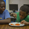 Eric Bonzar—The Morning Journal<br /> Eleven-year-old Teon Lenor cuts tomatoes for salsa as Abraham Thomas, 12, looks on, July, 27, 2016.