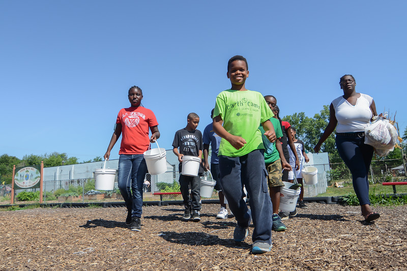 Eric Bonzar—The Morning Journal<br /> Jeff Baker leads the pack of young gardeners, who are carrying their haul of vegetables, July 27, 2016.
