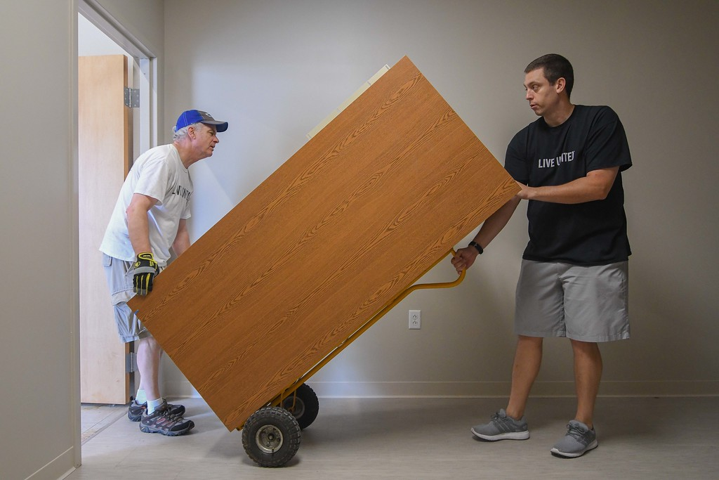 . Eric Bonzar�The Morning Journal Executive Director William Harper, left, and Marketing & Development Director Ryan Aroney move office furniture into the United Way of Greater Lorain County\'s new 642 Broadway Ave. office space, July 27, 2017.