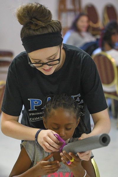 """Eric Bonzar—The Morning Journal<br /> Camp Counselor Jordan Keiffer, 16, helps 9-year-old Jalena Calhoun cut the base of her rocket, during PACE Foundations' """"Summer of Innovation"""" summer camp, Aug. 31, 2017."""