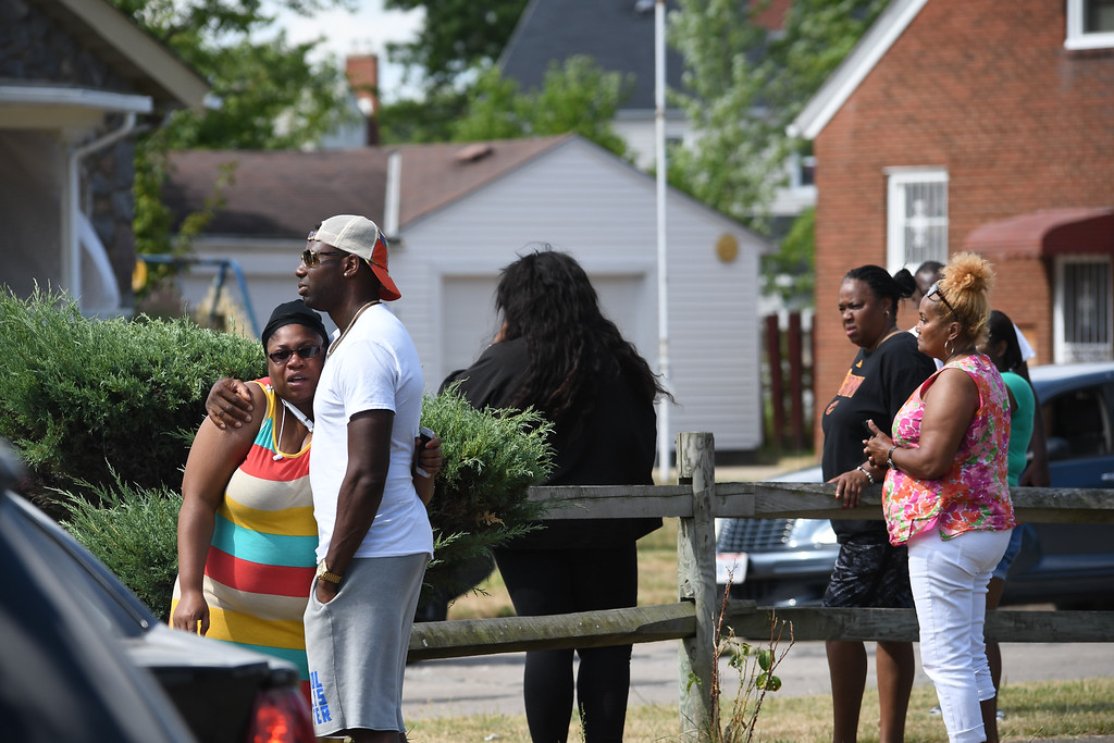 . Eric Bonzar�The Morning Journal Friends and family of 53-year-old Johnnie Whitfield gather across the street from his West 23rd Street home after receiving word of his death, Aug. 2, 2016.