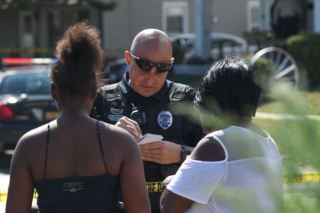 . Eric Bonzar�The Morning Journal Lorain police Officer Mark Pultrone gathers information during a homicide investigation, Aug. 2, 2016. Police are searching for answers in the death of 53-year-old Johnnie Whitfield, who was found dead in his West 23rd Street home.