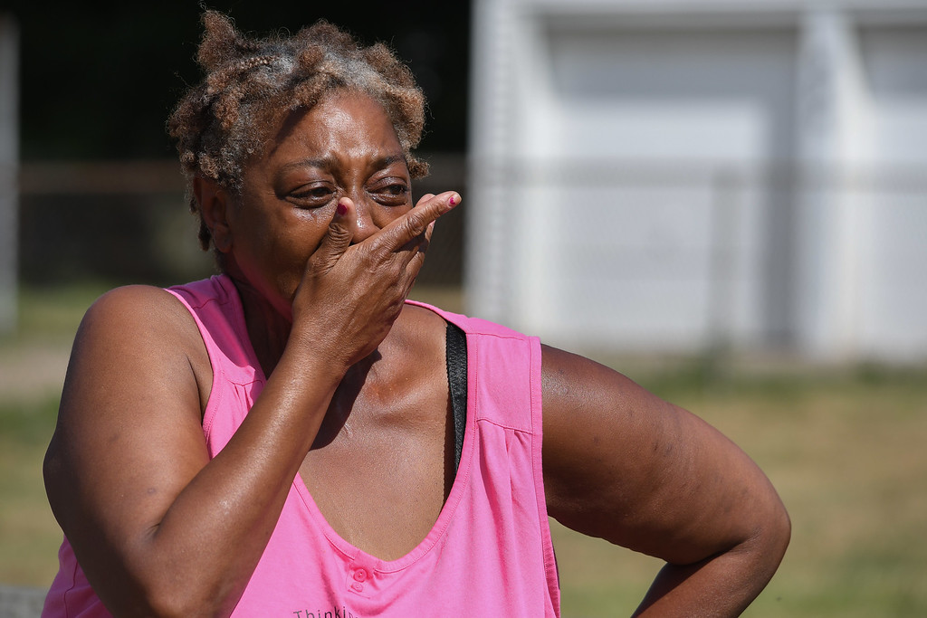 . Eric Bonzar�The Morning Journal A woman on scene fights back tears after hearing the news of Johnnie Whitfield\'s death, Aug. 2, 2016.