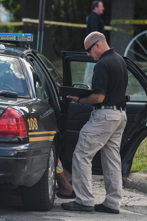 . Eric Bonzar�The Morning Journal Lorain police Sgt. Dennis Camarillo questions a woman at the scene of a homicide investigation, Aug. 2, 2016.