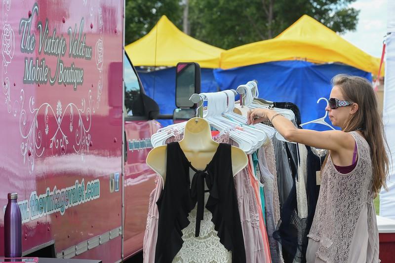 Eric Bonzar—The Morning Journal<br /> Marissa Zimmerman, owner of The Vintage Valet LLC Mobile Boutique, rearranges a rack of her vintage wares, for sale, during The Vermilion Beach Market, at Sherod Park, Aug. 4, 2017.
