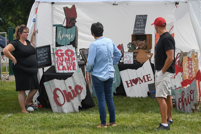 Eric Bonzar—The Morning Journal<br /> Carly Schaub, of Indian Lake Creations, sells vintage signs made from 100 percent recycled wood during The Vermilion Beach Market, at Sherod Park, Aug. 4, 2017.