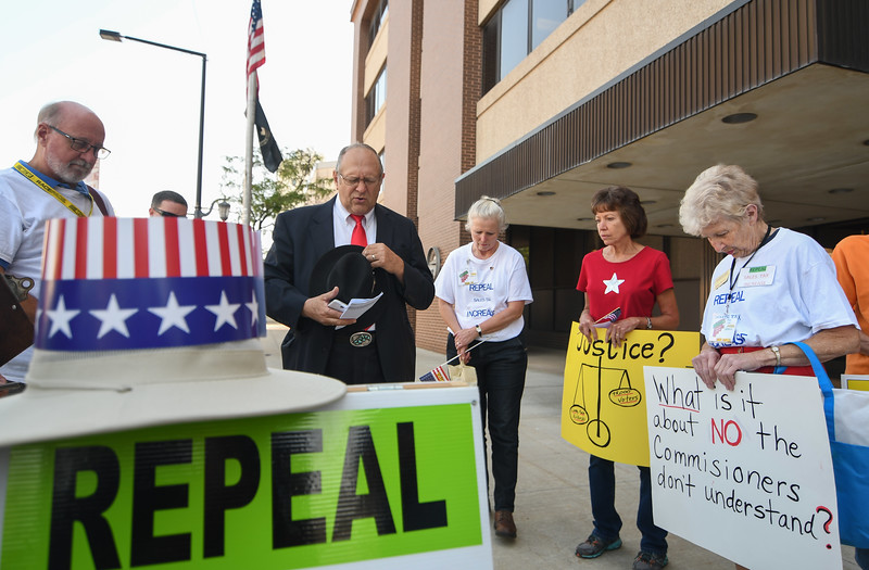 Eric Bonzar—The Morning Journal<br /> Rev. Rick Young, of Elyria, leads the Repeal the Sales Tax Committee in prayer, outside of the Lorain County Administration Building, Aug. 9, 2017. Young and fellow members of the committee protested the county-wide sales tax increase prior to the Lorain County Commissioners meeting.