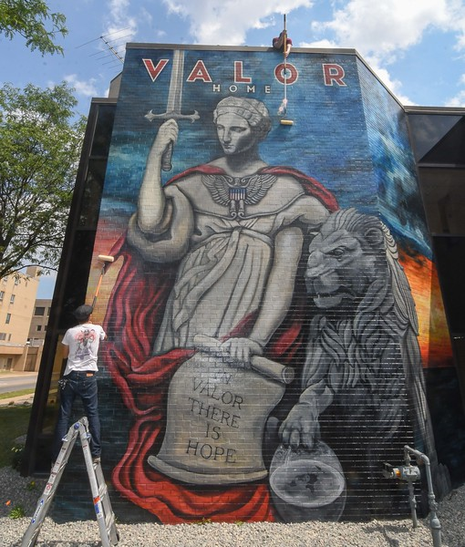 Eric Bonzar—The Morning Journal<br /> Local artists Mike Sekletar, and Brian Goodwin, of Amherst, add the finishing touch to the Valor Home mural: a coat of clear to protect the artists' work from the elements and potential vandals, Aug. 10, 2017. The pair of life-long friends spent roughly two months' time painting the western outside wall of the 221 W. 21st St. transitional facility to honor local military veterans.