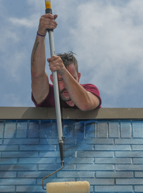 . Eric Bonzar�The Morning Journal From the roof of the Valor Home, Brian Goodwin uses a roller to add a coat of sealant to the mural.