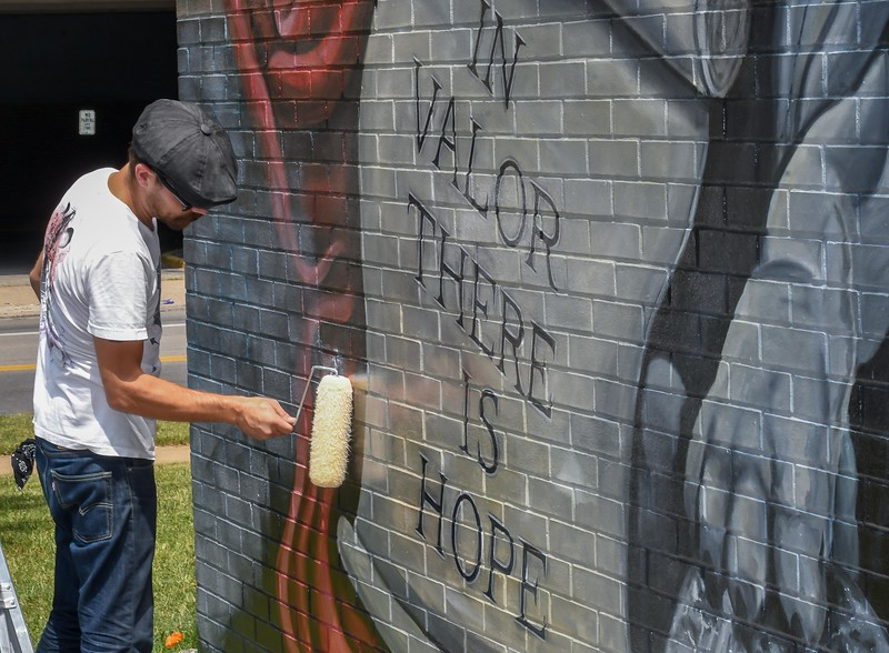 Eric Bonzar—The Morning Journal<br /> Local artist Mike Sekletar, of Amherst, adds a coat of clear to the Valor Home mural he and life-long friend Brian Goodwin painted to honor local military veterans, Aug. 10, 2017.