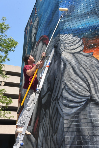Eric Bonzar—The Morning Journal<br /> Local artist Brian Goodwin , of Amherst, adds a coat of clear to the Valor Home mural he and life-long friend Mike Sekletar painted to honor local military veterans, Aug. 10, 2017.