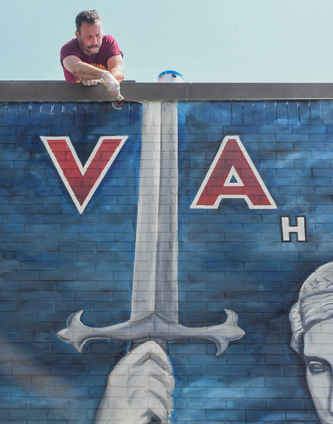 Eric Bonzar—The Morning Journal<br /> From the roof of the Valor Home, Brian Goodwin uses a paint brush to add a coat of sealant to the mural.