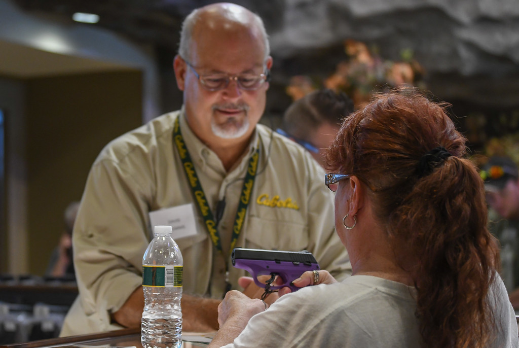 . Eric Bonzar�The Morning Journal A customer looks at firearm for purchase during the grand opening of Cabela\'s Avon store, Aug. 11, 2016.