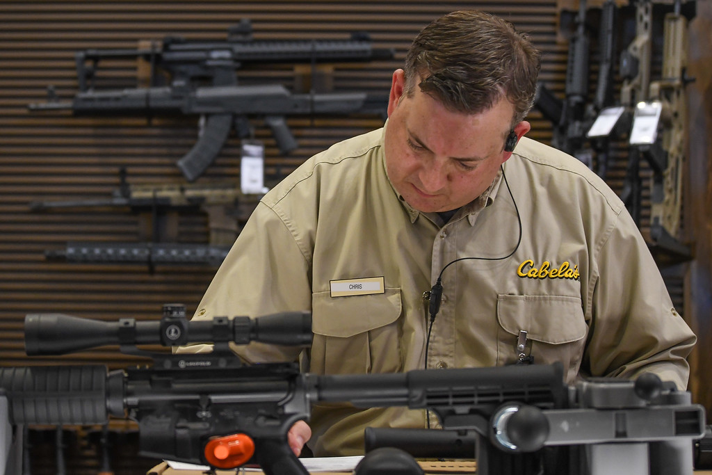 . Eric Bonzar�The Morning Journal A Cabela\'s associate fills out the necessary paperwork for a firearms purchase.