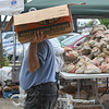 Eric Bonzar—The Morning Journal<br /> A patron of El Centro de Servicios Sociales, Inc.'s farmer's market carries his haul of groceries on his shoulder, Aug. 24, 2017. The market, at the organization's 2800 Pearl Ave. facility, was held in collaboration with Second Harvest Food Bank of North Central Ohio.