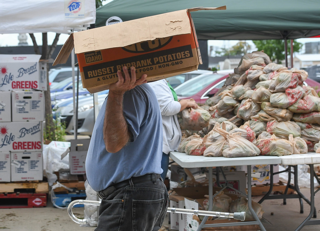 . Eric Bonzar�The Morning Journal A patron of El Centro de Servicios Sociales, Inc.\'s farmer\'s market carries his haul of groceries on his shoulder, Aug. 24, 2017. The market, at the organization\'s 2800 Pearl Ave. facility, was held in collaboration with Second Harvest Food Bank of North Central Ohio.