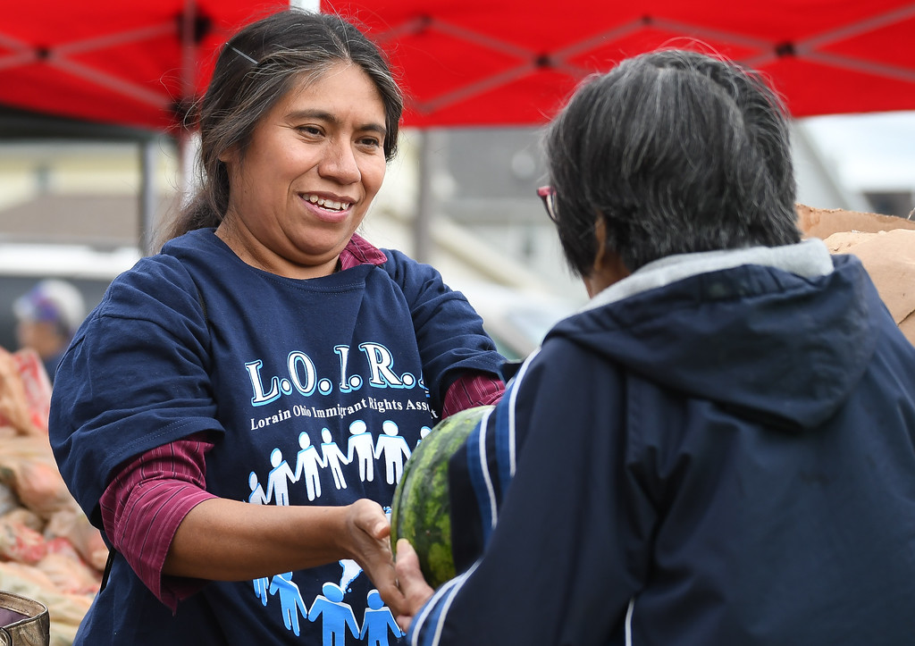 . Eric Bonzar�The Morning Journal Volunteer Leouijilda Avagón, of Lorain, hands out watermelons during El Centro de Servicios Sociales, Inc.\'s farmer\'s market, Aug. 24, 2017. Avagón was volunteering on behalf of the Lorain Ohio Immigrant Rights Association.