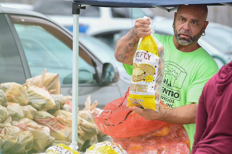 Eric Bonzar—The Morning Journal<br /> Johnny Maldonado, money management case worker for El Centro de Servicios Sociales, Inc., hands out 10 pound bags of potatoes to patrons during the 2800 Pearl Ave. organization's farmer's market, in collaboration with Second Harvest Food Bank of North Central Ohio,   Aug. 24, 2017.