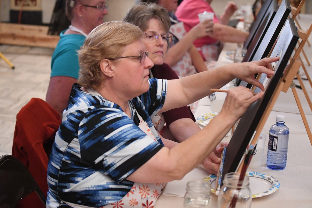 . Eric Bonzar�The Morning Journal Shelley Harmych, of Amherst, outlines the Lorain Lighthouse during Whet Your Palette\'s paint night at the Lorain Palace Theater, Aug. 24, 2017.