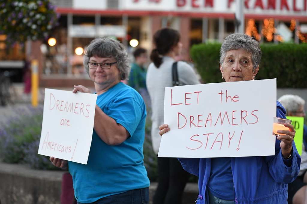 . Eric Bonzar�The Morning Journal Leesa Husar, of Lorain, left, and Judy Kruger, of Oberlin stand on the corner of Oberlin\'s Tappan Square to protest President Donald Trump\'s recension of former President Barack Obama\'s Deferred Action for Childhood Arrivals (DACA) program, Sept. 5, 2017.