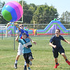 "Eric Bonzar—The Morning Journal<br /> Seventh-graders Aden Gregory, 13, left, Trent Roose, 12, center, and Tyler Smith, 12, work together to keep an inflatable beach ball in the air, during United Way's ""United We Sweat Field Day"" event held at Midview High School's Ross Field, Sept. 13, 2016."