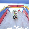 "Eric Bonzar—The Morning Journal<br /> Eighth-grader Moe Shinnawi, 13, slides his way to the finish line on one of multiple, inflatable, obstacle courses set up at Midview High School's Ross Field, Sept. 13, 2016. The obstacle courses were one of many fitness stations and wellness activities offered during United Way's ""United We Sweat Field Day"" event for middle school students."